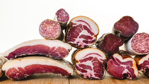 a bunch of different types of cured meat on cutting boards and stacked in a way that displays the fat marbling and ingredients