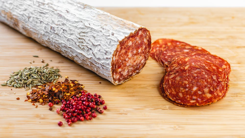 a whole chub of soppressata salami on cutting board with soppressata slices next to it and herbs and spices in the foreground.