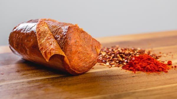 A close up side shot of n'duja salami on a cutting board with spices next to it.