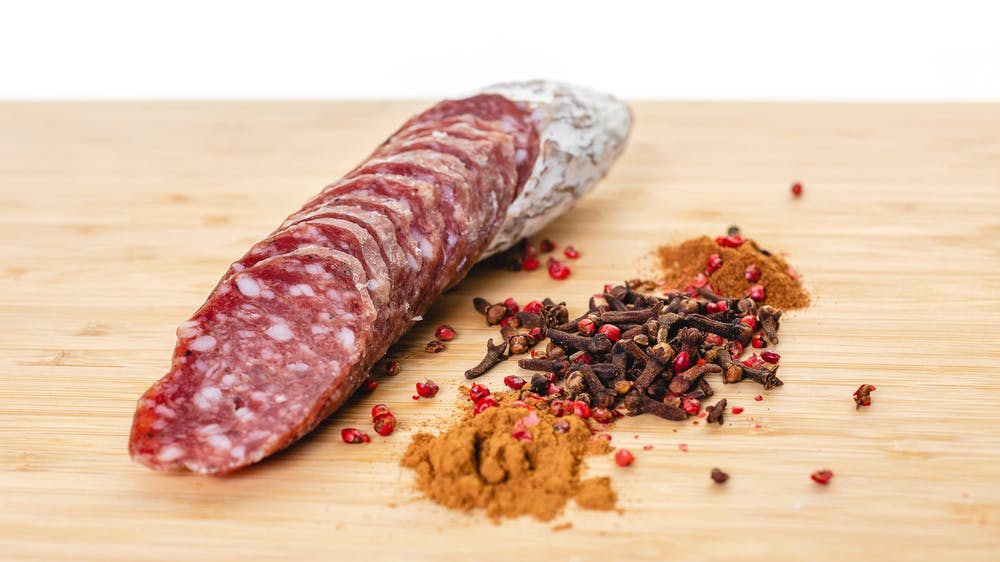 Rosette de Lyon Salami cut into pieces on a cutting board with herbs and spices next to it.