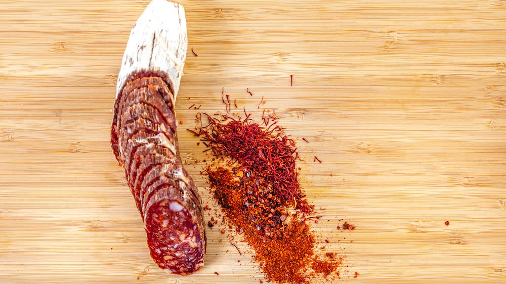 Saucisson Basque Salami cut into pieces on a cutting board with spices and herbs to the right of it
