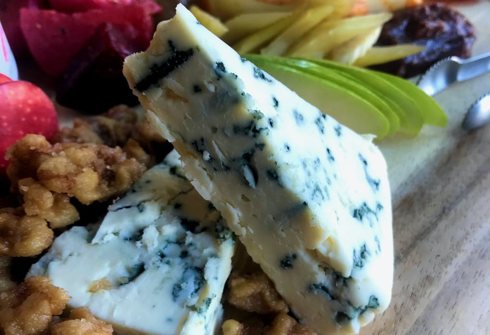 A close up picture of blue cheese on a charcuterie board surrounded candied walnuts and accompaniments.