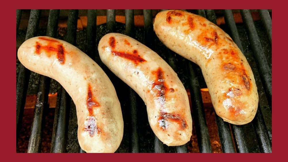 Bratwursts being cooked on a grill with grill marks on them.