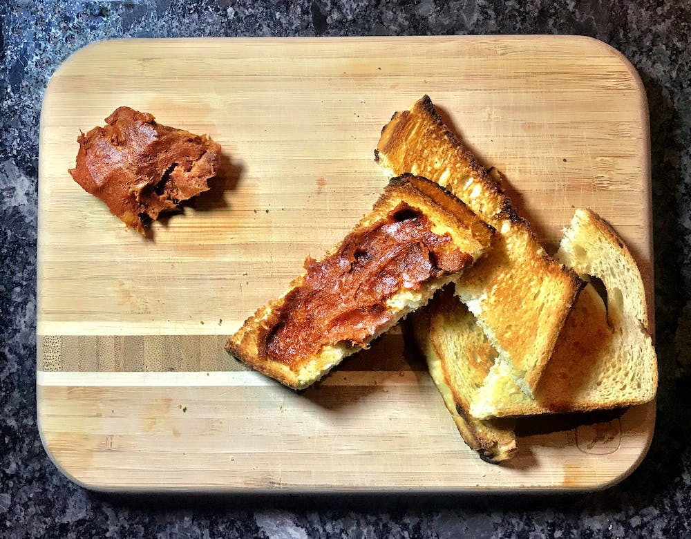 four pieces of crispy toasted bread on a cutting board with nduja spread on one piece.