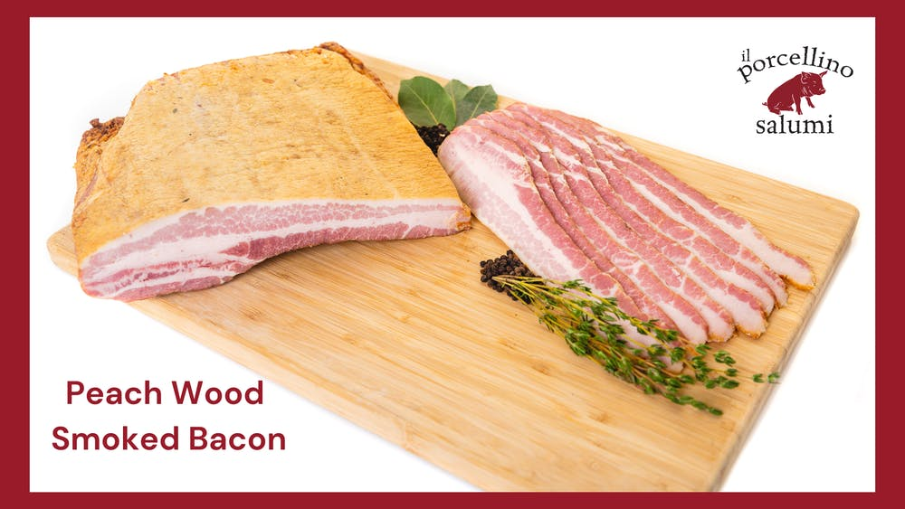 il porcellino salumi's Peach Wood Smoked Bacon as a whole chub and sliced strips on a cutting board with herbs and spices.