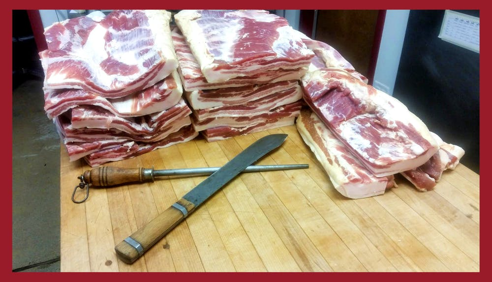 Several stacks of pork bellies on a butcher table before they're prepared for dry curing to make bacon.