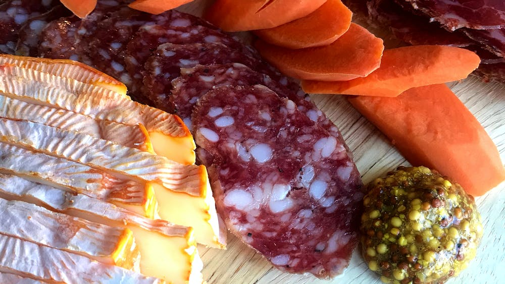 A close picture of il porcellino's rosette de lyon salami cut into slices on a cutting board. The salami is surrounded by pickled carrots, cheese and mustard.