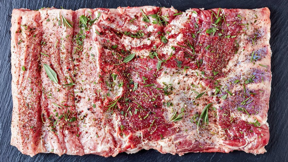 A whole pork belly covered with herbs and spices before it is rolled and tied to make porchetta.