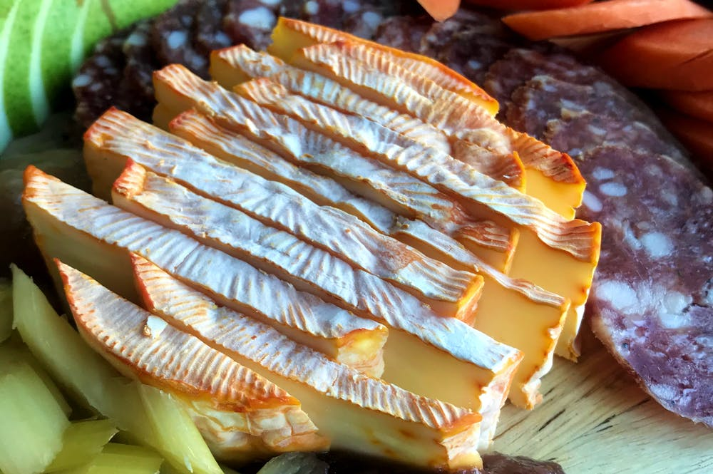 A close up image of ColoRouge soft cheese from MouCo in Colorado on a charcuterie board.