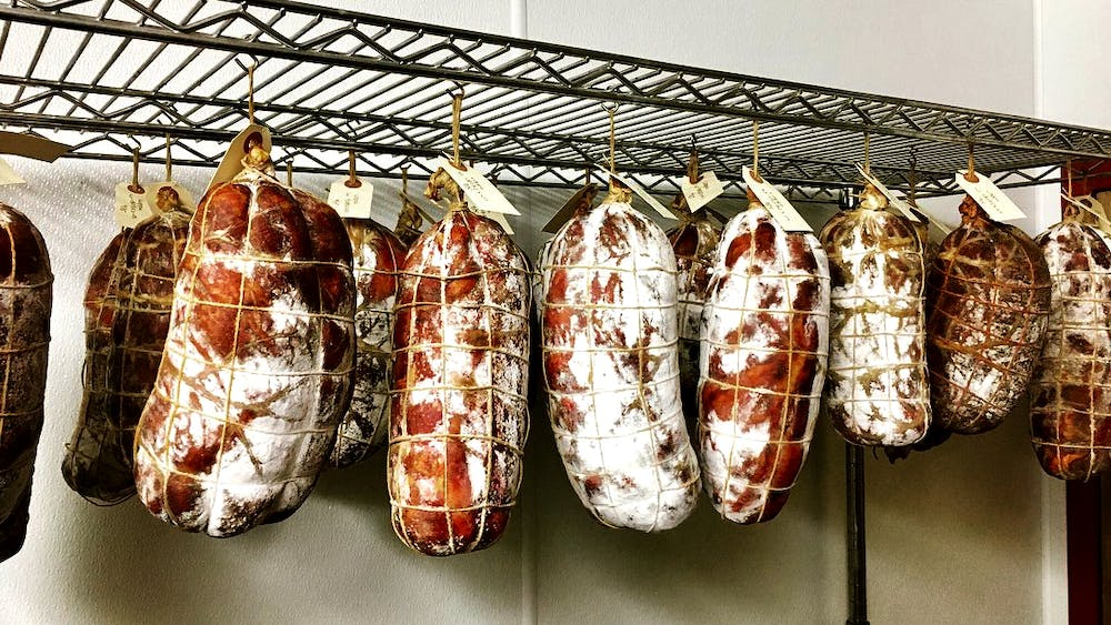 il porcellino salumi's large format salami hanging in the drying room to display the different colors of protective mold that form.