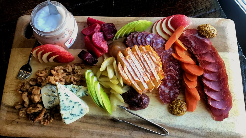 il porcellino salumi's fall harvest charcuterie board with cured meats, cheese, fruits and pickled vegetables.