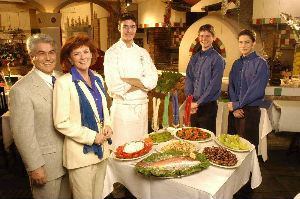 a group of people standing in front of a plate of food