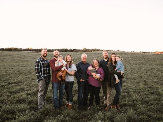 a group of people standing in the grass