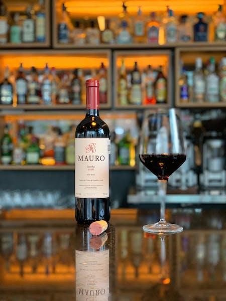 una botella y copa de vino en la mesa del bar