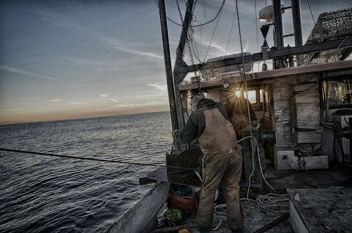 a lobsterman standing next to a body of water