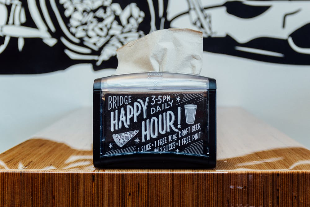 a napkin dispenser and a happy hour sign on it