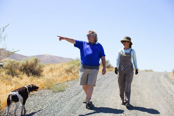 a man and a dog walking on a dirt road