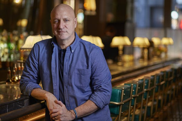 Tom Colicchio sitting at a table