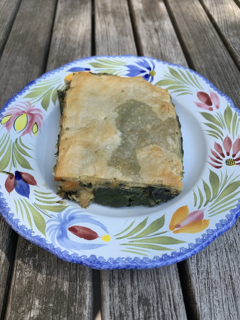 a piece of spanakopita on a wooden table