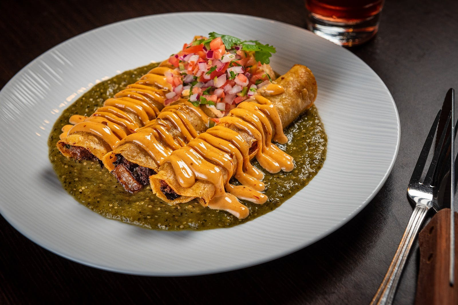 taquitos with sauce on a plate