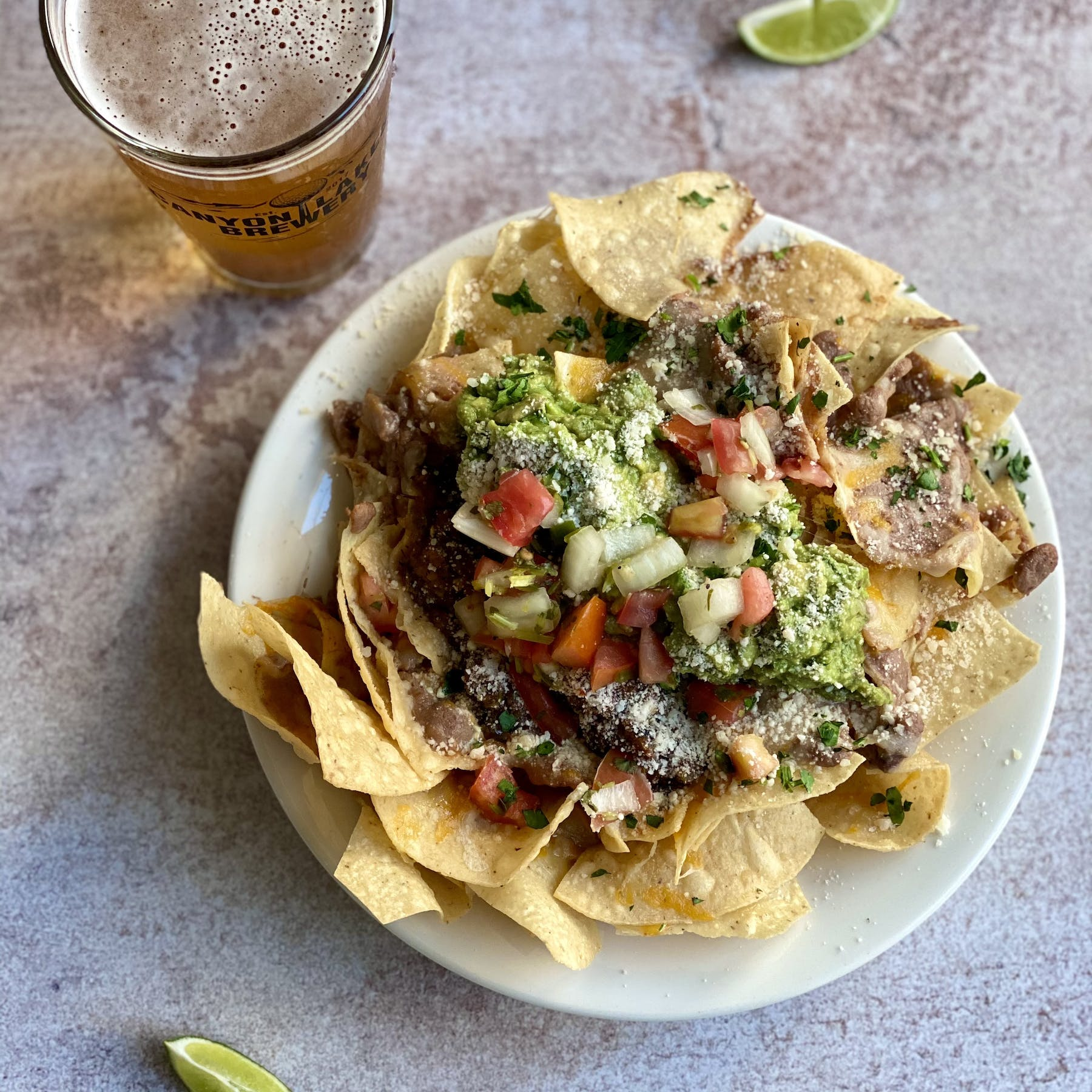 a plate of nachos with a pint of beer