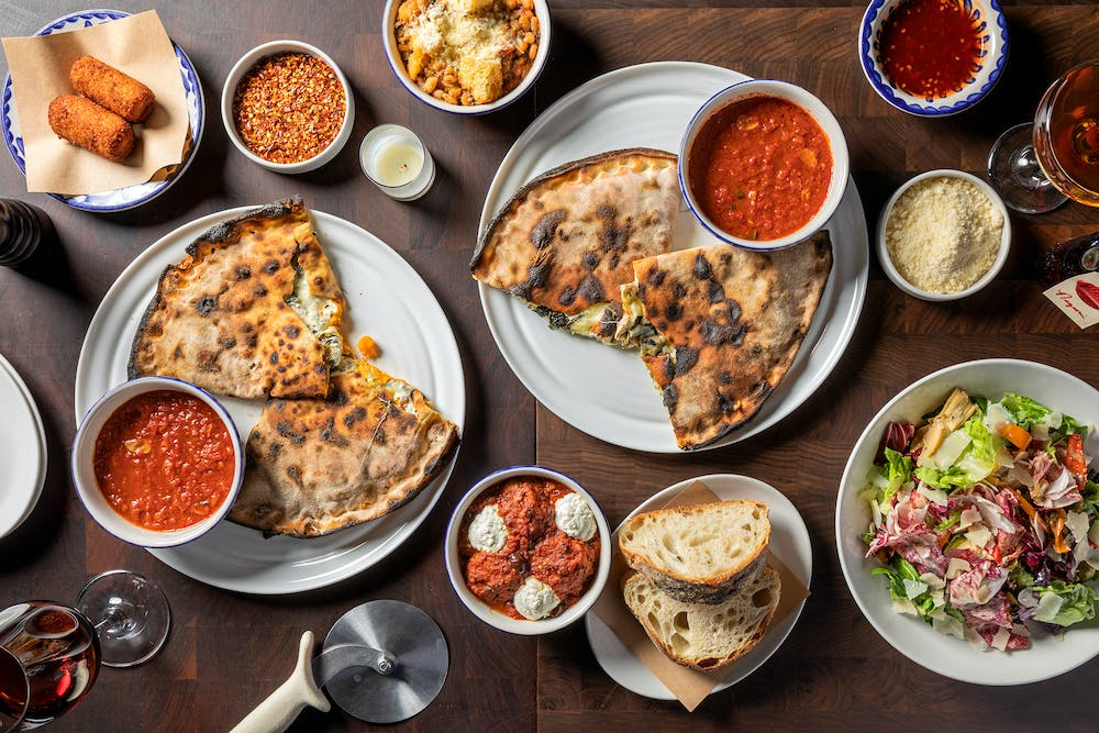 a table filled with different calzones and sides