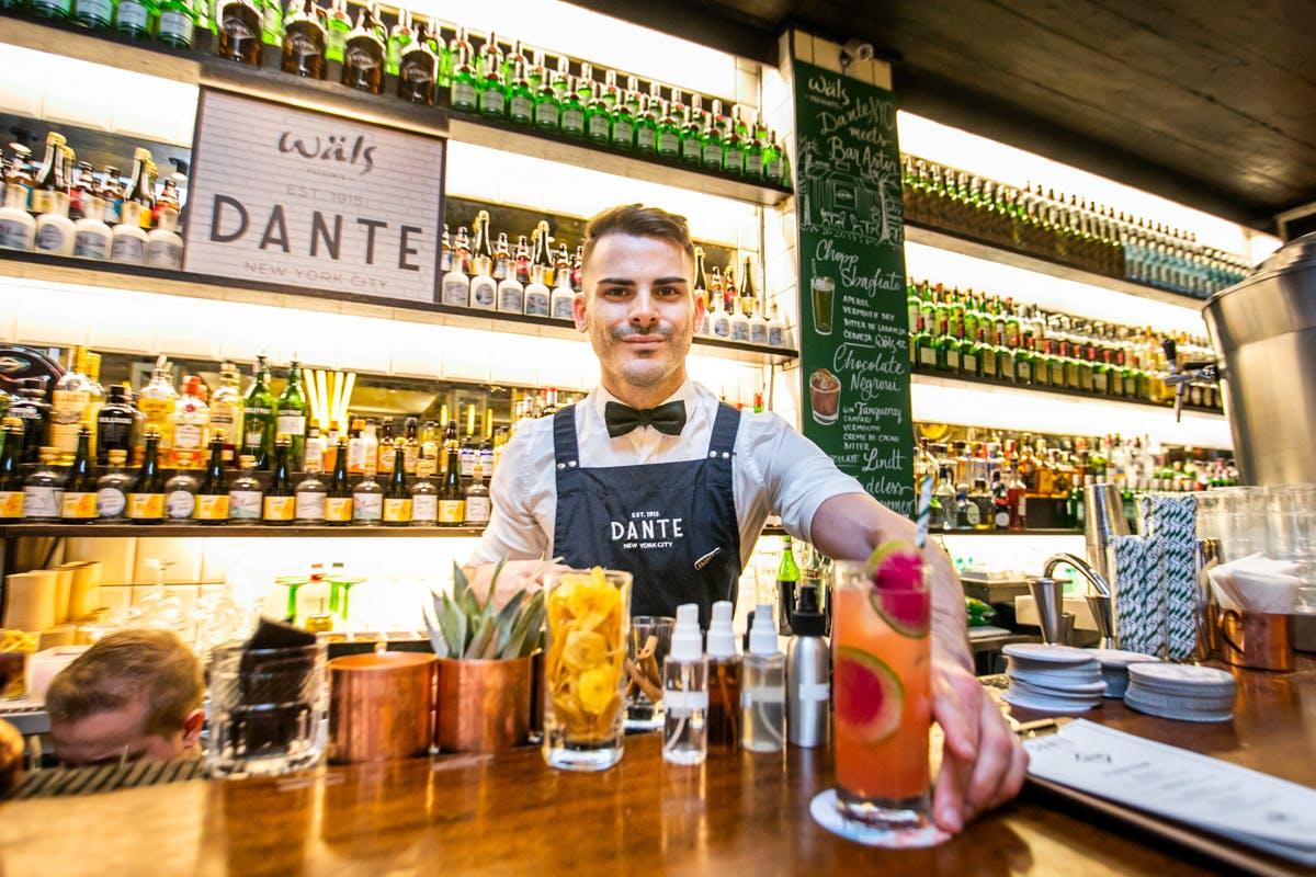 a bartender displaying cocktails