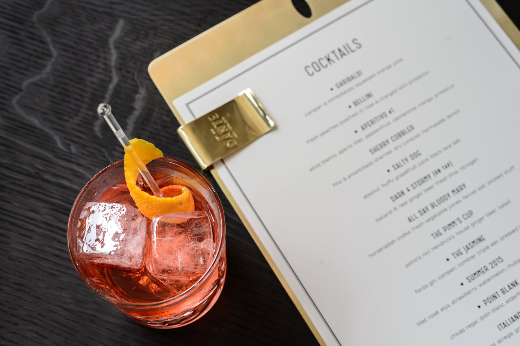 a menu an a cocktail on a table