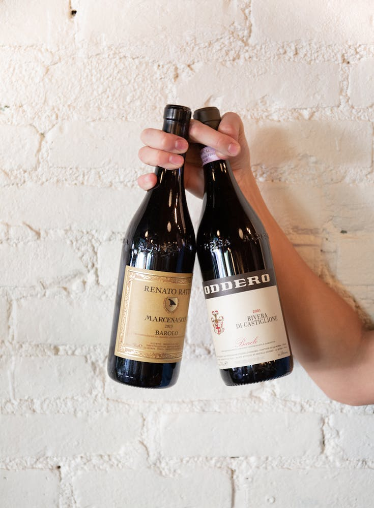 a hand holding a bottle of wine