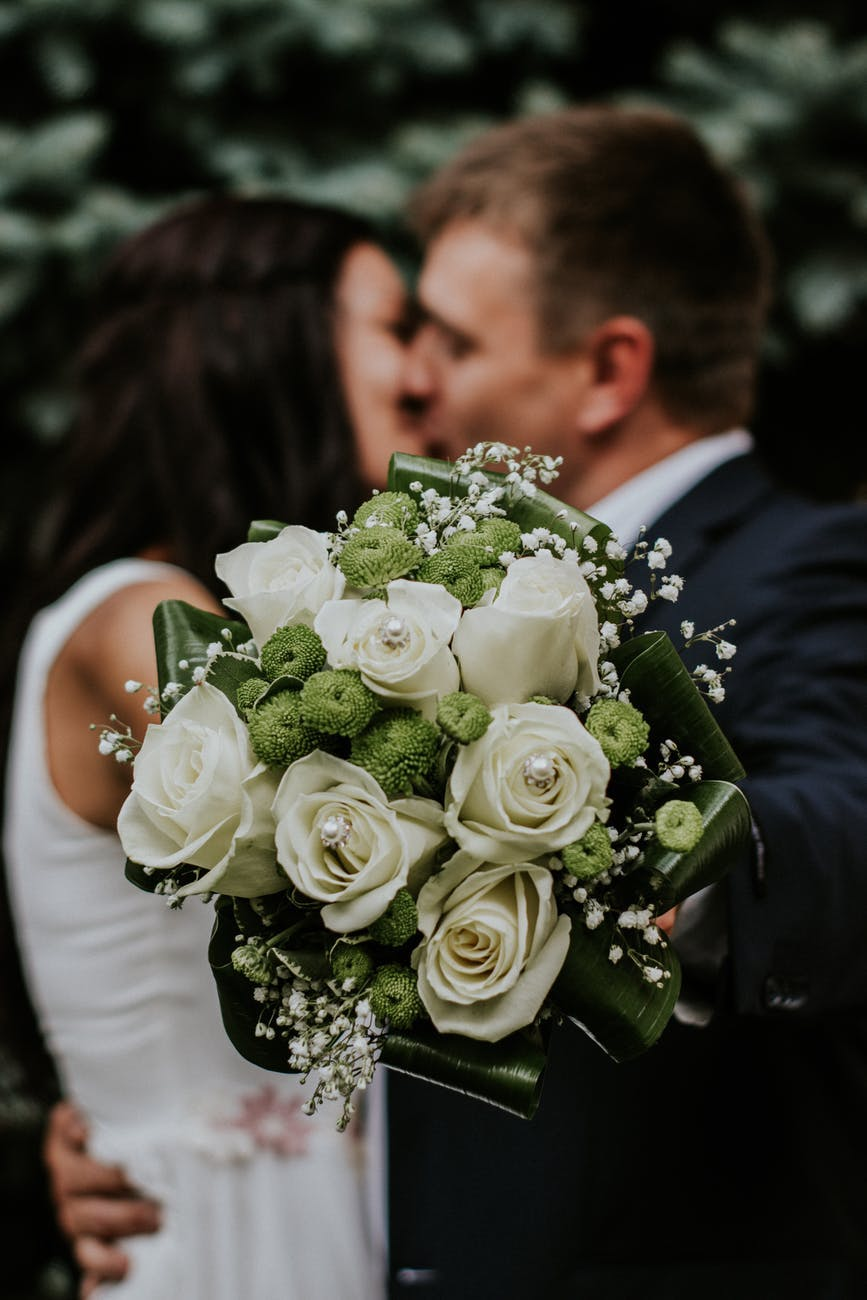 a bouquet of flowers with a couple kissing on the background