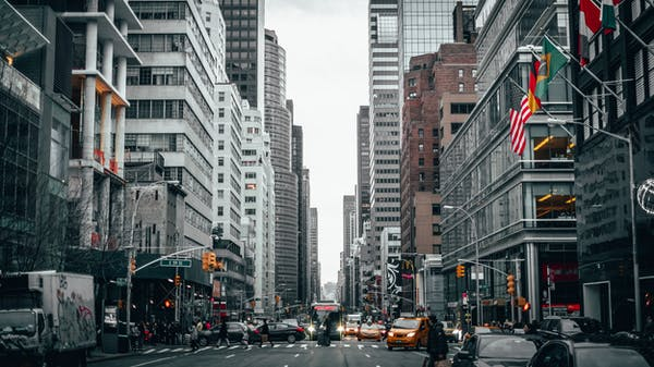a city street filled with traffic surrounded by tall buildings