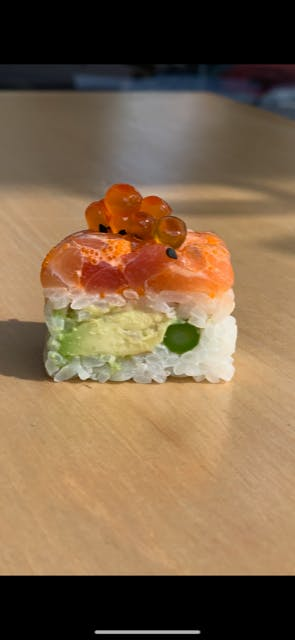 a piece of cake sitting on top of sushi on a table
