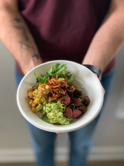 a person holding a bowl of food