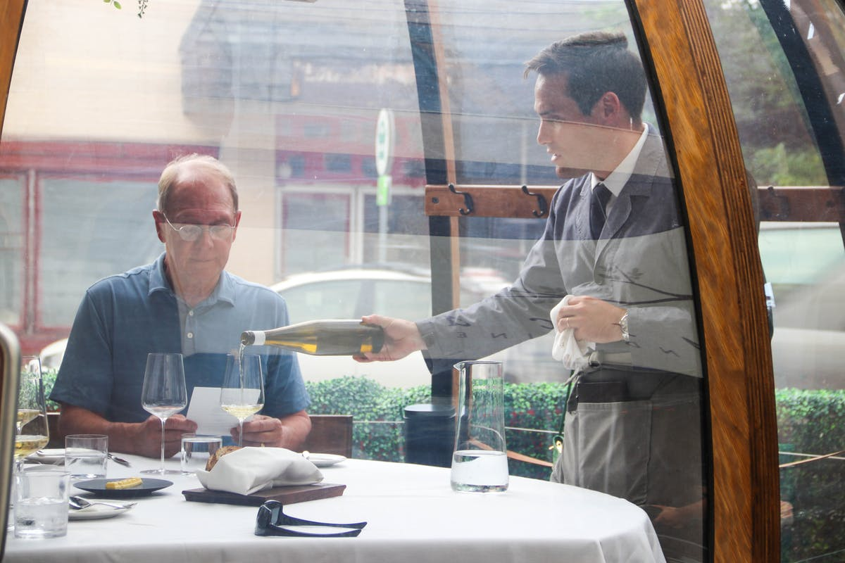 a person sitting at a table with wine glasses