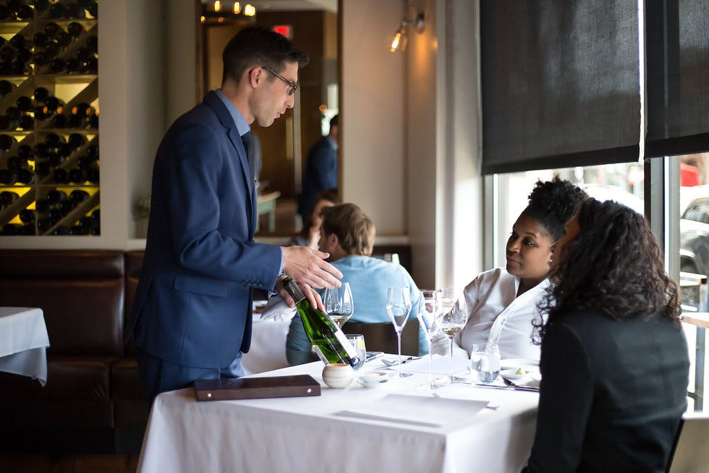 a waiter showing a bottle of wine to the customers