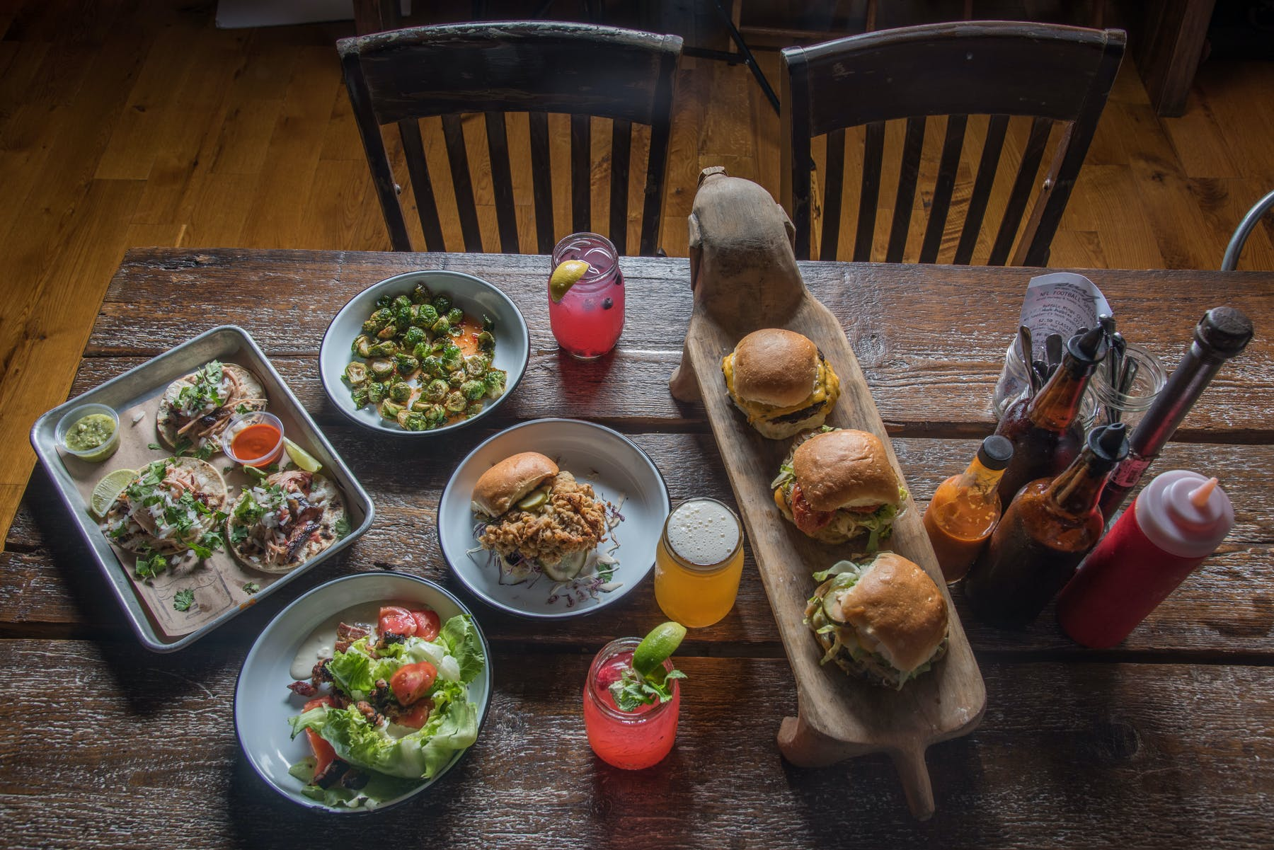 plates of burgers, drinks, and tacos on a table