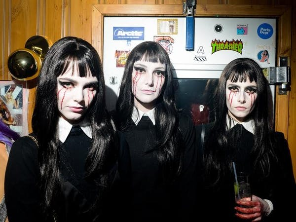 Three young women in a halloween goth getup