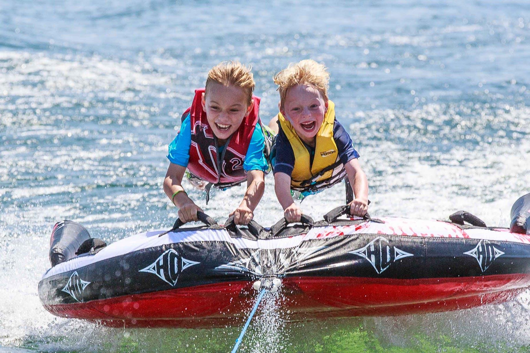 2 kids tubing on a lake