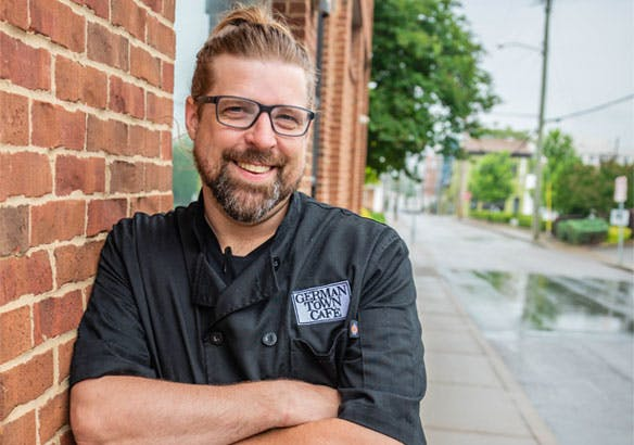 Chef Jeff Martin standing in front of the brick building of Germantown Cafe