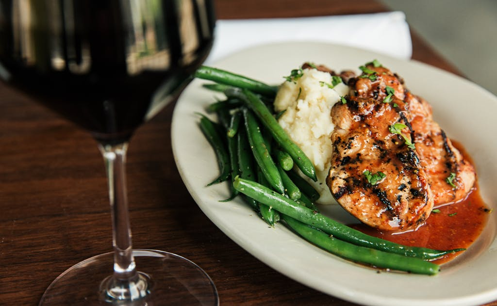 A view of plated plum pork with green beans, mashed potatoes and a glass of red wine on a wooden table.
