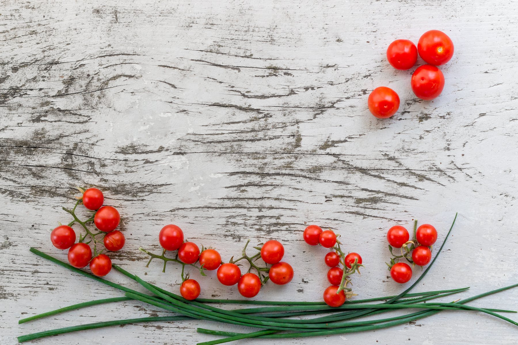 a close up of red berries lying on a wooden table