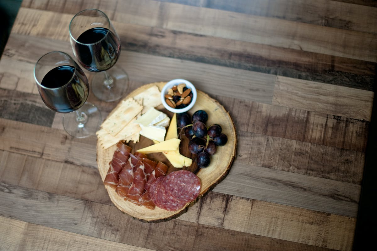 a wooden board with prosciutto, salami, grapes, cheese, crackers a glass of wine