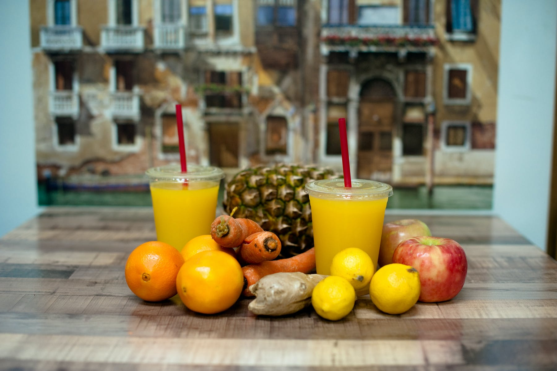 two orange juices sitting on a wooden table with other fruits