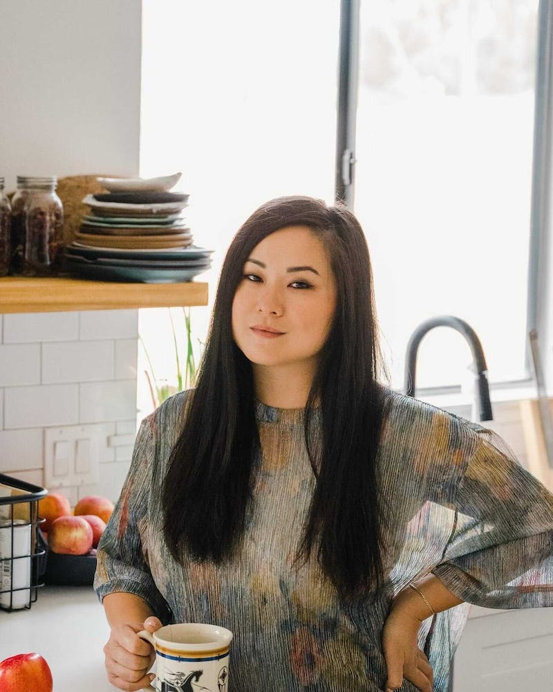 Jenny Gao sitting at a table in front of a window