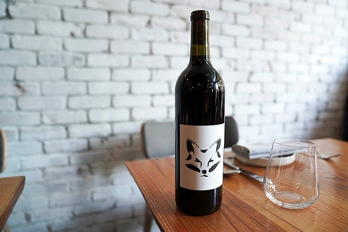 a bottle of wine sitting on top of a wooden table