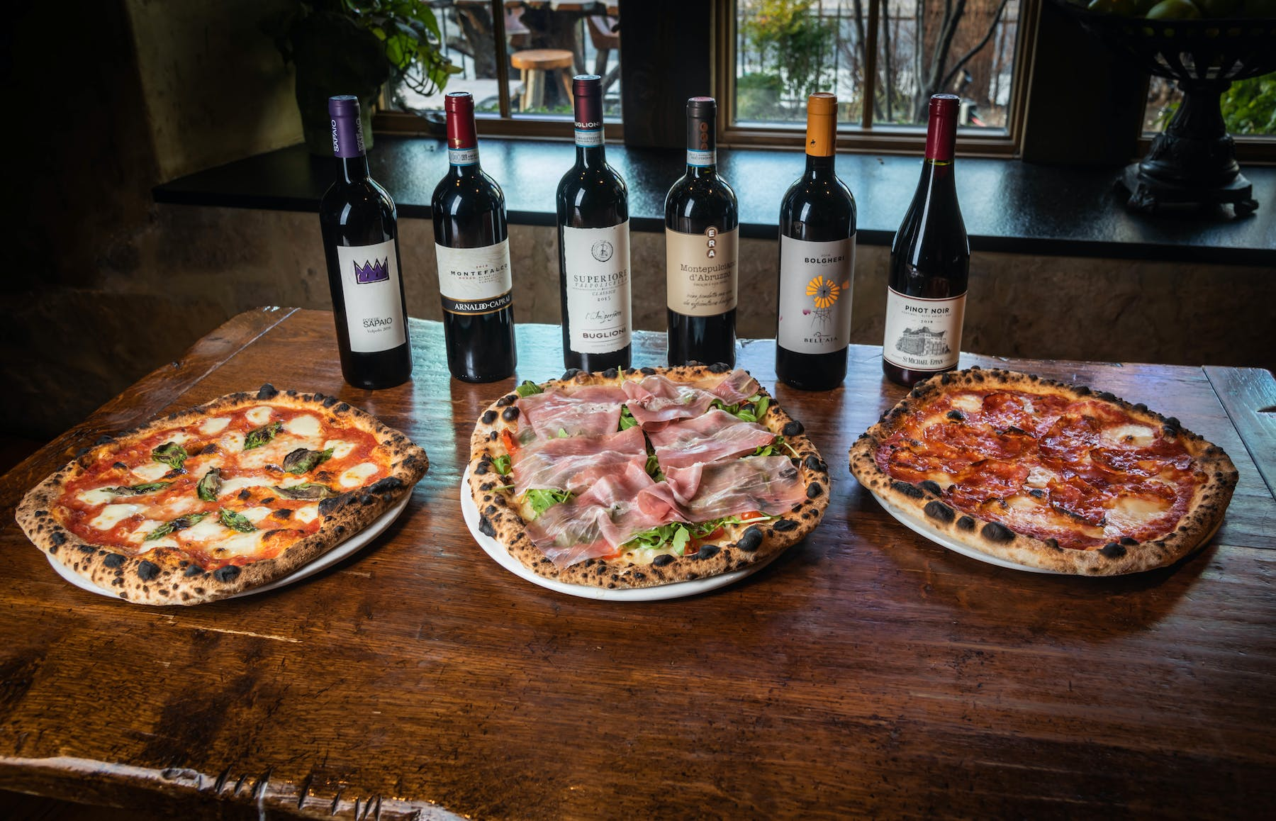 a pizza sitting on top of a table next to a bottle of wine