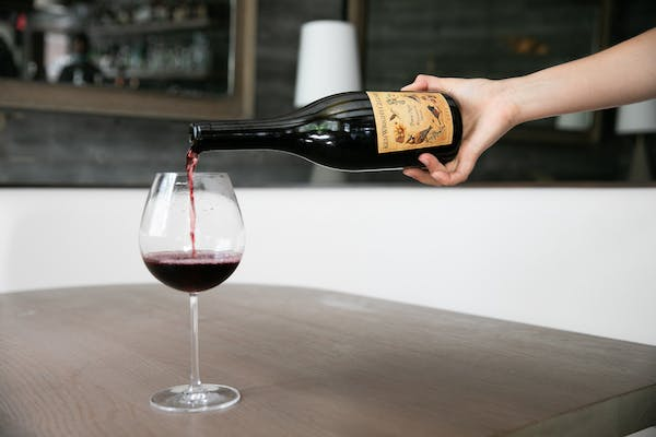 a hand holding a glass of wine