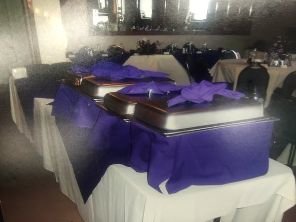 a room filled with a table topped with purple table cloth