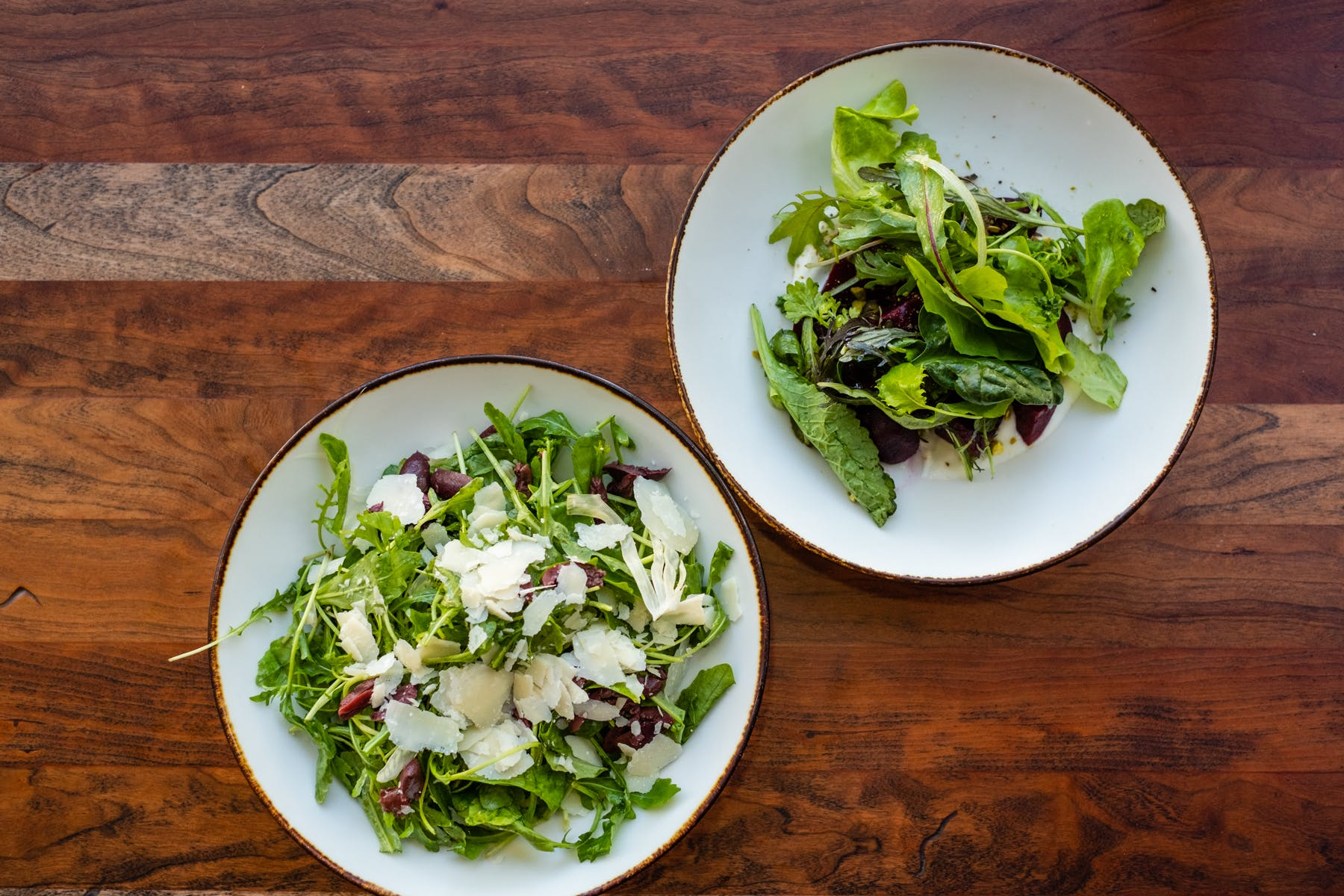 a bowl of salad on a plate on a wooden table