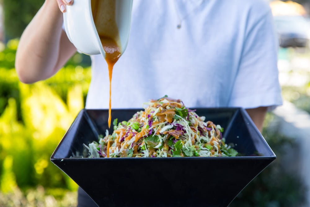 a person standing in front of a bowl of salad